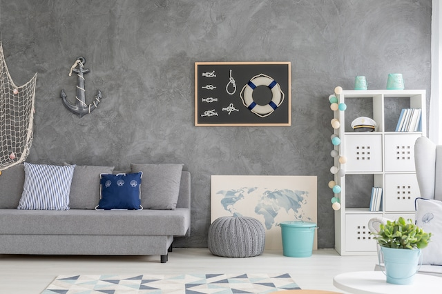 A photo of one part of a room with a grey wall with a grey couch in front of it. The wall has several nautical decor objects on it, including a net, an anchor, and a frame with a life saving ring and rope knots. Next to the couch is a map of the world and a white bookshelf with a captain's hat and books on it. In front of the bookshelf is a white chair and a plant in a light blue pot.