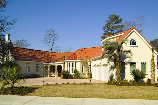 The exterior of a one-story Mediterranean style home with a white stucco exterior and red tile roof.