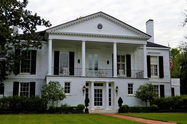 The front exterior of a white, plantation style home with an American flag on the side. There is a brick pathway leading up to the house with green grass to each side.