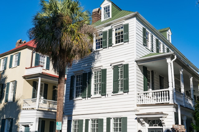 A photo of two historic Charleston style homes, one white with green shutters, one tan with orange roofing.