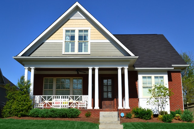 The exterior of a Cape Cod style house with red brick and vinyl siding.