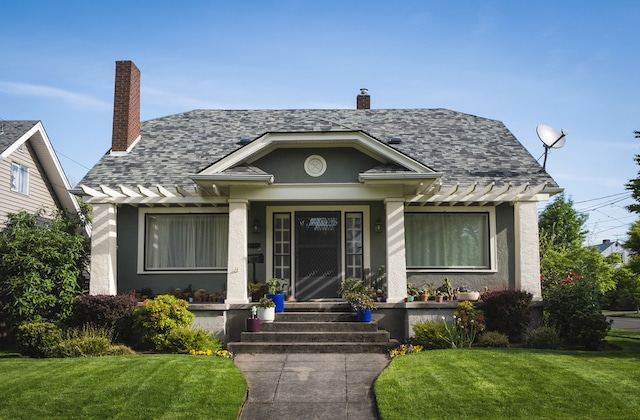 The exterior of a grey American craftsman bungalow style home with a green lawn.