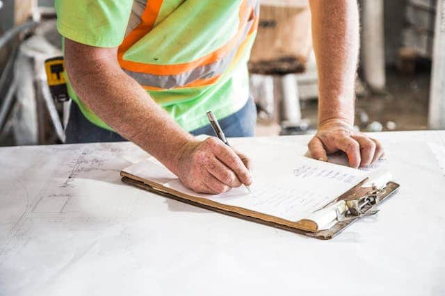 A construction worker in a construction vest is writing on a clipboard on top of a table with blueprints on it.