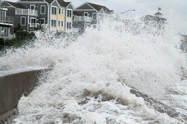 Waves crashing against beachfront housing during a hurricane