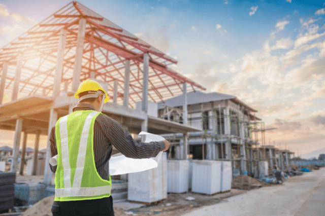 construction worker in a yellow vest and yellow hard hat is looking at blueprints in front of a home that's being constructed.