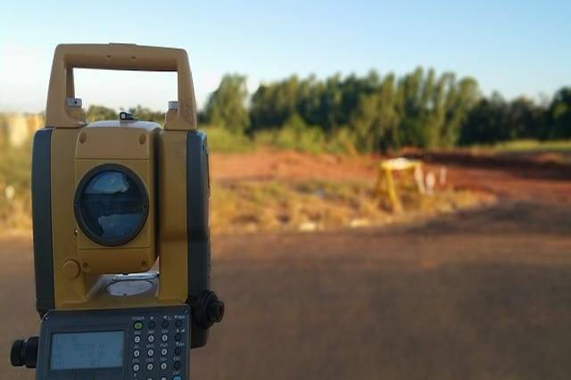 A land surveying machine with a plot of land in the background